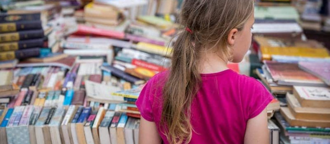 girl-looking-at-books-for-sale-on-a-street-market--DVNCZ2X (1)